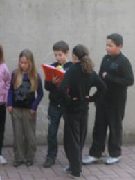 Le président (qui tient dans ses mains le cahier du conseil) rassemble des enfants lors de la récréation, pour tenter d'apporter une médiation à leur conflit.